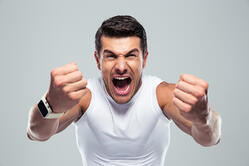 Excited fitness man shouting at camera over gray background